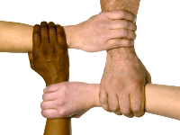 Multi-racial hands linked together.